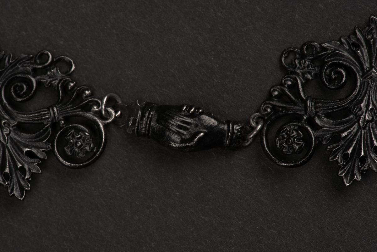 Svart halsband av gjutjärn. Halsbandet består av omväxlande större och mindre utsirade länkar i nygotisk stil, som är sammanfästa med runda små länkar. Mitt fram hänger ett större likformat kors, som är något skadat. Spännet är utformat som två händer.
