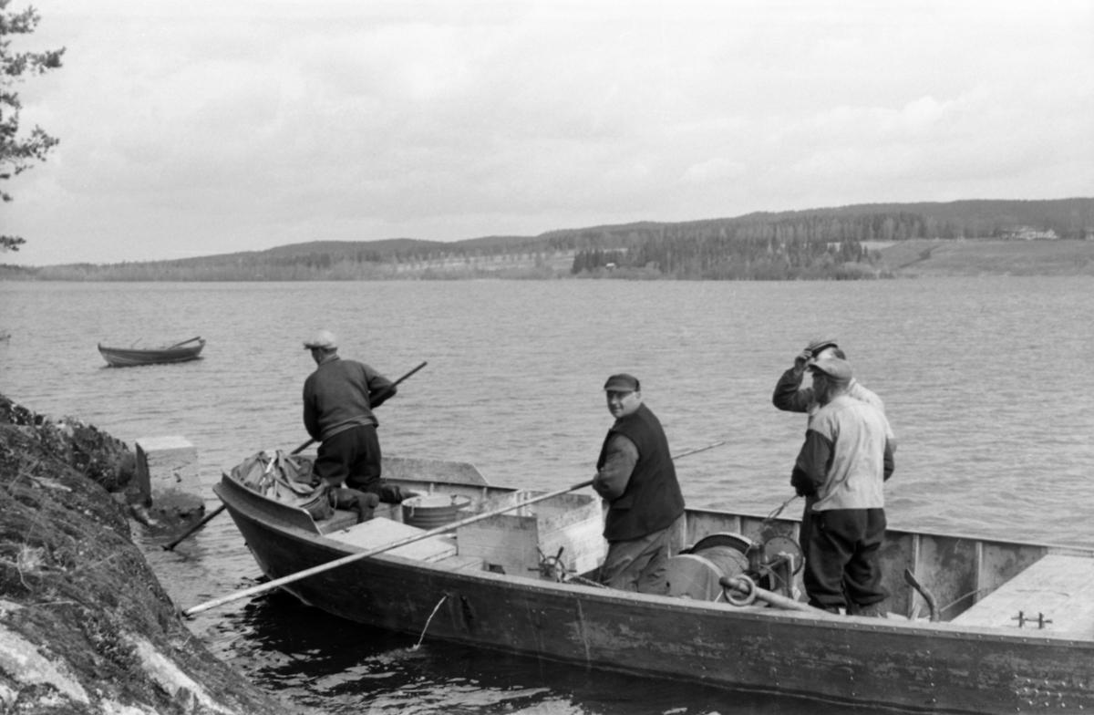 Fra tømmerfløtinga på Vingersjøen øst for Kongsvinger i mai 1956.  Fotografiet viser Glomme Fellesfløtingsforenings den gang nye varpebåt på denne sjøen.  Båten er fotografert like inntil land, på et sted der en bergskrent skrår bratt ut i vannet.  To av fløterne i båten holder farkosten unna berget ved hjelp av fløterhakene sine.  To andre står i samtale.  Båten later til å være utført i stål og ha innvendig motor.  Innenbords skimter vi en svær trommel med stålvaier og ei diger trosse (anker), antakelig brukt under håndtering av store tunge tømmerbommer på sjøen.  Av underteksten framgår det at denne varpebåten var ny i 1956, i og samme album inneholder et fotografi av spillflåtefløting på Vingersjøen i 1955 (SJF. 1990-01887).  Mye tyder på at fotografen her har dokumentert et teknisk metodeskifte i fløtinga på dette stedet.  En robåt ligger ankret et stykke fra land og et stykke fra varpebåten.  I bakgrunnen ses jordbrukslandskapet på østsida av Vingersjøen med bakenforliggende barskogkledde åser.