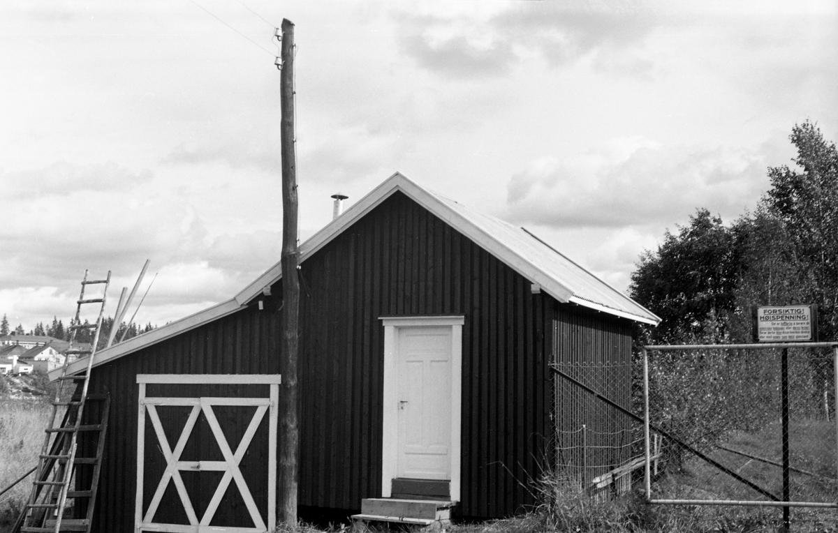Koie med garasje eller verksted. Skilt med advarsel om høyspenning. Kurudsand ved Glomma, Kongsvinger, Hedmark.