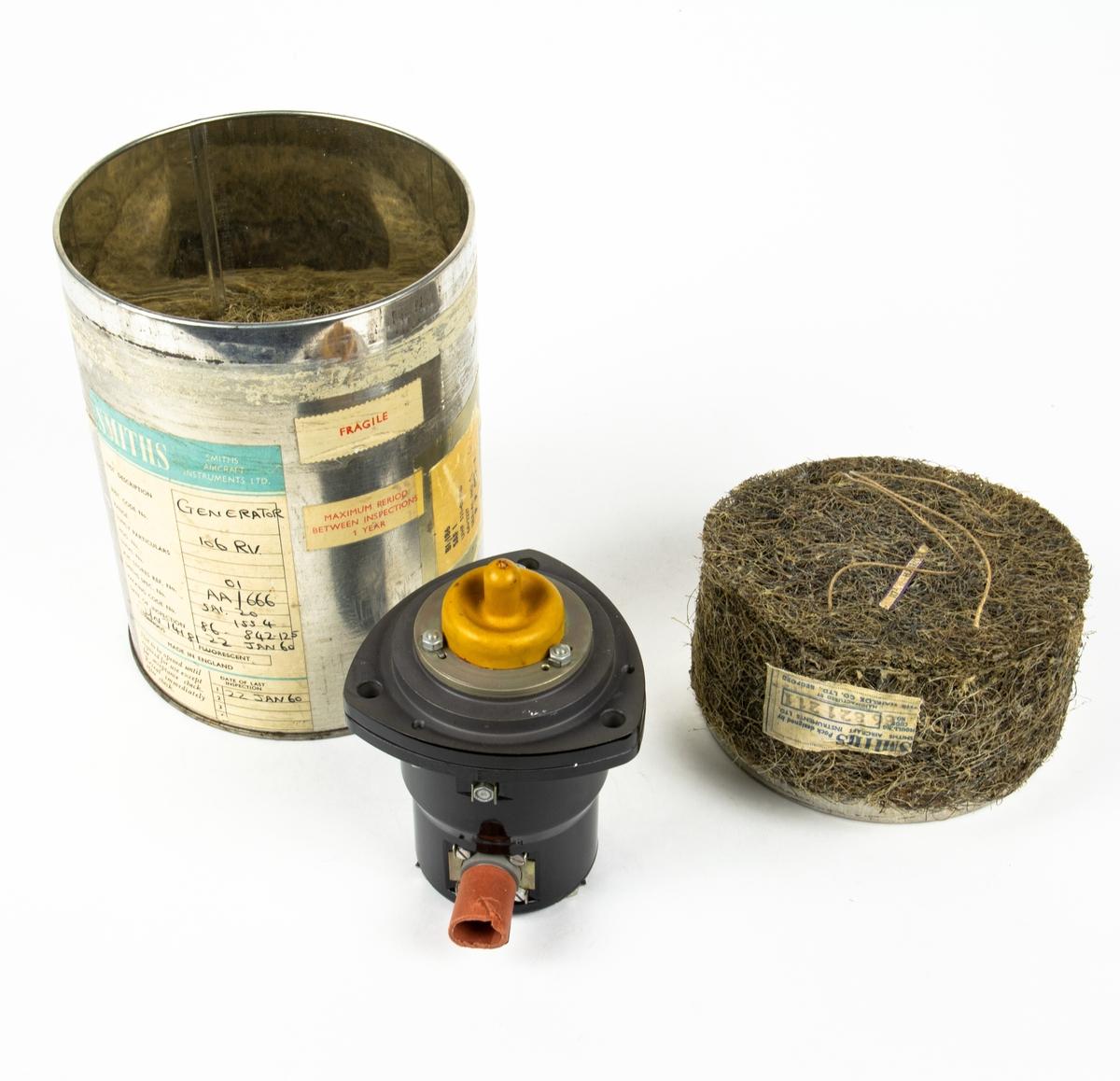 Varvräknargenerator Smiths 106RV. Oanvänd med originalförpackning och förseglingar. Generatorns hölje är gjort av svartmålat gjutgods, Drevet har kvar sitt transportskydd (gult gummi), liksom kabelgenomföringen (röd papp).  Förpackningen består av en cylindrisk plåtburk med etiketter. I burken finns förpackningsmaterial av formgjutet tagel, tillvekat av The Hairlok Co.