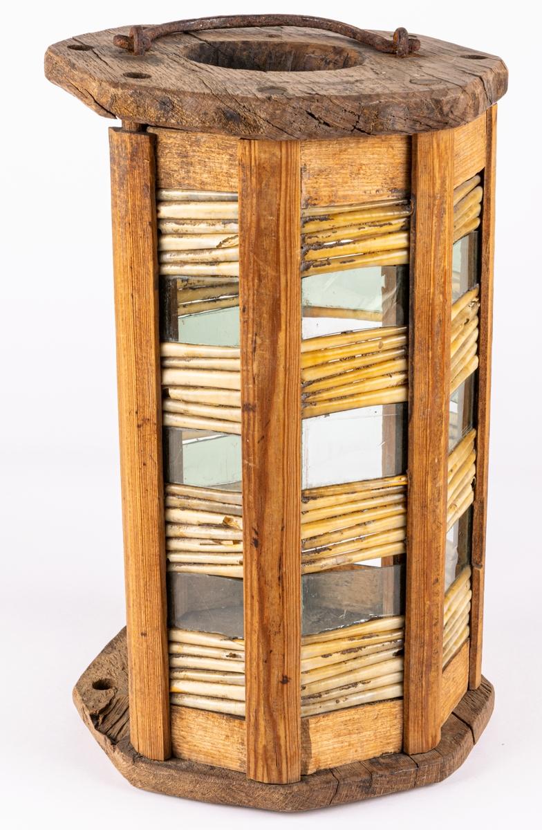 Handlykta, 7-sidig med lodräta stolpar med glas och fjäderpennor mellan. En av stolparna med glasen på båda sidor saknas. Ingen ljushållare, alltså troligen avsedd för lös liten lampa. Eventuellt ekträ.