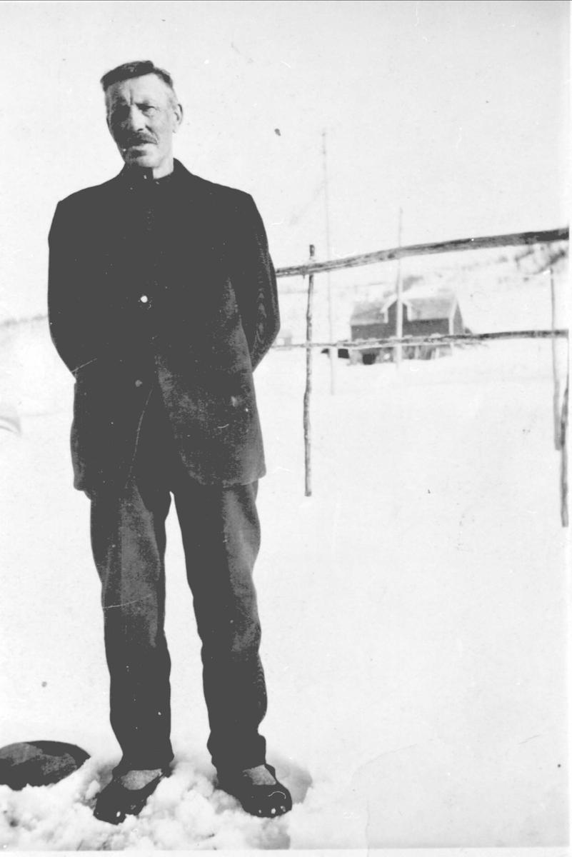 Amatørportrett av eldre mann stående i snøen. Fjøs i bakgrunnen.