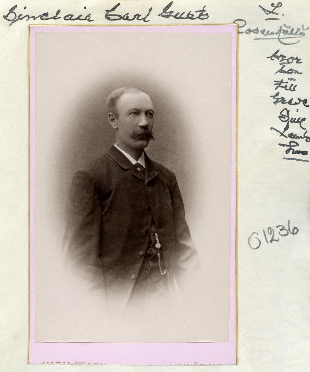 """Porträtt av Greve Carl Gustaf Sinclair. Född den 3 juni 1849 vid Karlshovs säteri i Älvestad som förstfödde sonen till greve Israel Malcolm Sinclair och grevinnan Alfhild Spens. Inledde sin militära karriär som kadett vid Militärhögskolan Karlberg i Solna 1868 och stationerades senare vid Andra Livgrenadjärregementet i Linköping där han 1888 uppnådde kaptens grad. Erhöll avsked ur krigstjänsten 1901. Gift den 14 december 1889 och bosatte sig i Mjölby med Emilia """"Elly"""" Charlotta Isidora Smedberg, dotter till läroverksadjunkten Carl Adolf Isidor Hilarion Smedberg och Emelie Augusta Charlotta Lindh. Parets dotter Claire Alfhild Emelie Henriette föddes i Torpa där familjen levde en tid innan de flyttade vidare till Säby, Jönköpings län. Carl Gustaf Sinclair avled i hjärtsjukdom den 4 augusti 1919 i Visby."""