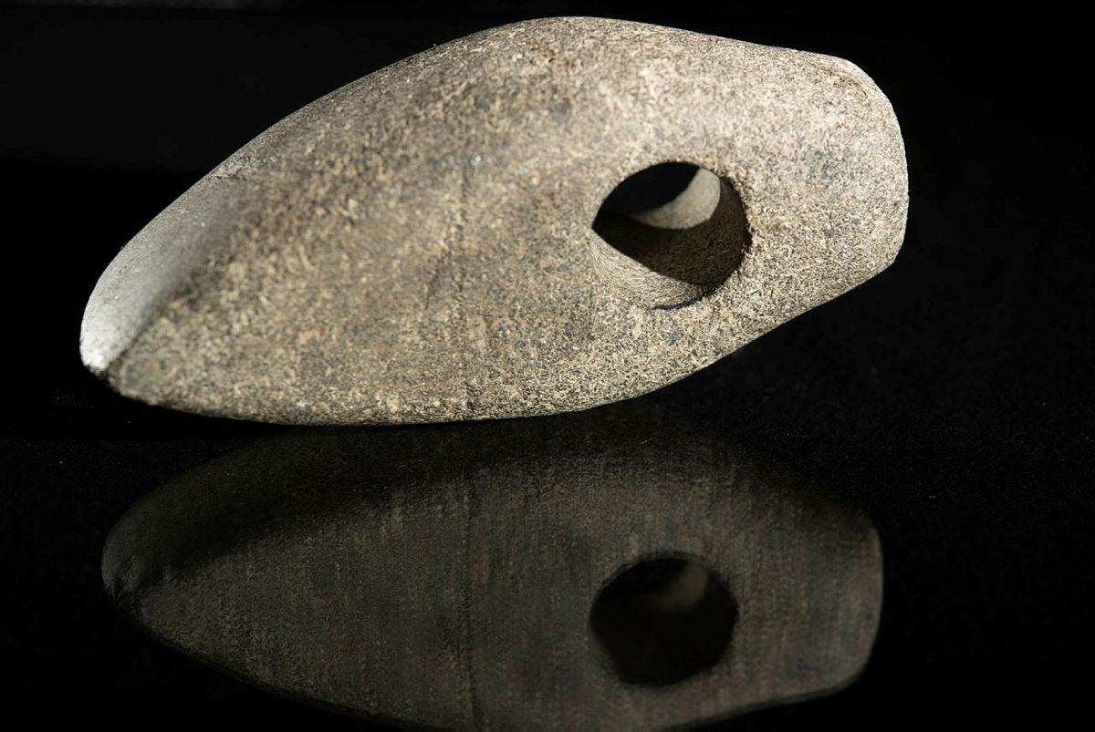 Rombyxa. Ovanlig typ. Undersidan bågig. Eggen nedåtsvängd. På ovansidan spår efter rörborrning strax invid skafthålet.