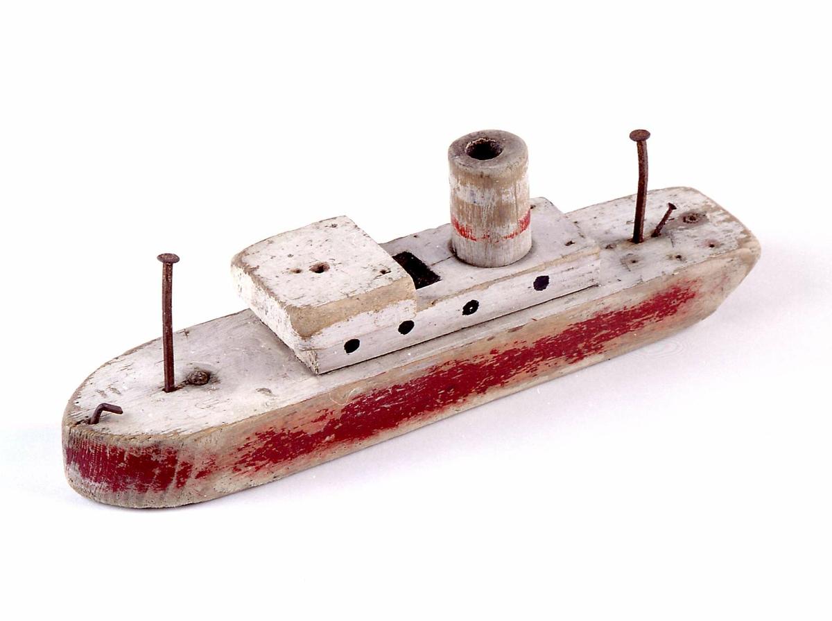 Lekebåt av tre. Trebiter er spikret sammen. Båten har hvit grunnfarge, med rødt sideparti. Malingen er noe avflasset.