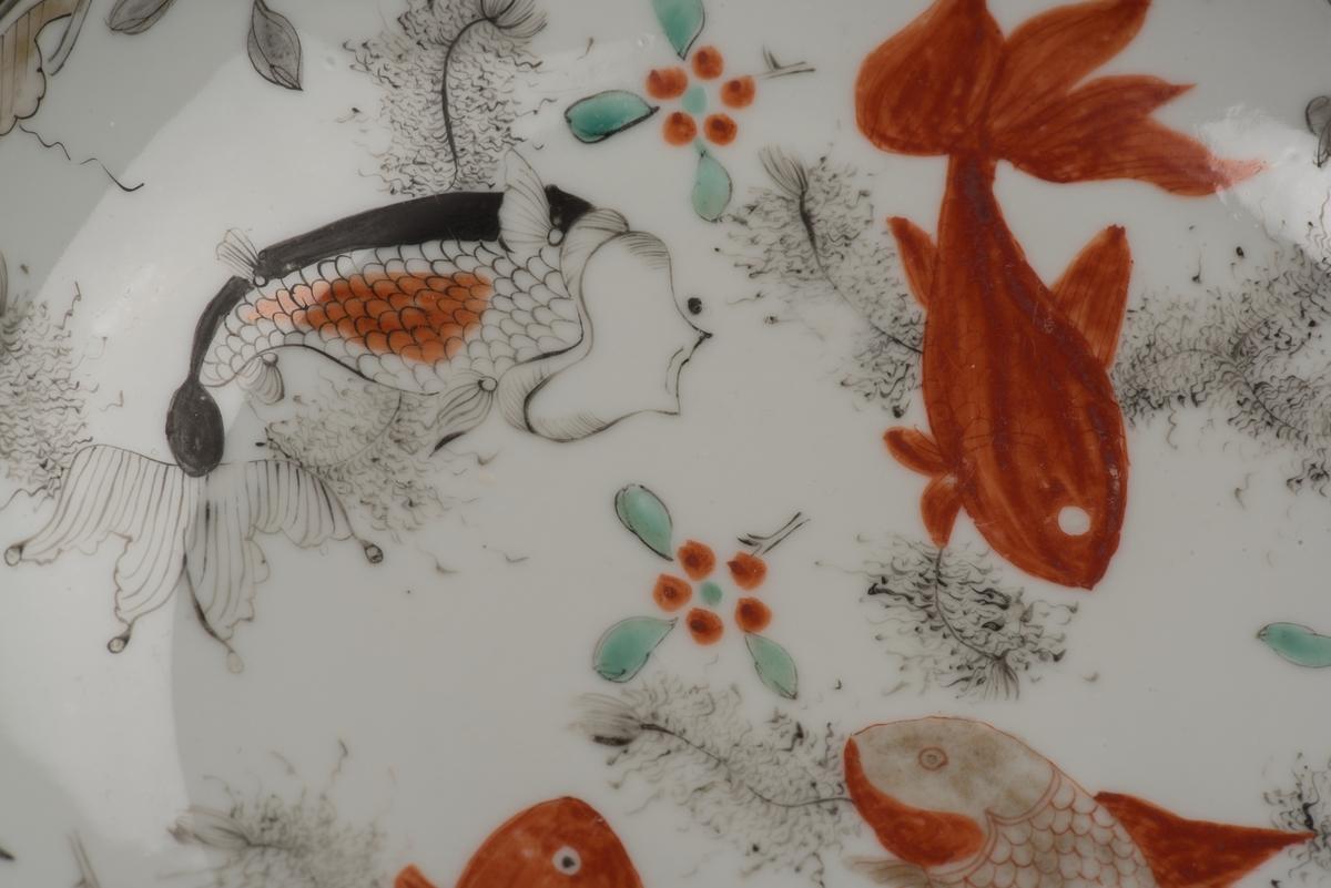 Runt fat av vitt porslin.  Bemålad med mångfärgad, polykrom, dekor i form av fyra karpfiskar, blommor och blad. Fatet har en låg skålform utan bräm samt en oglaserad fotring. På undersidan finns en text om att tallriken tillhört den Gradmanska hemmet.