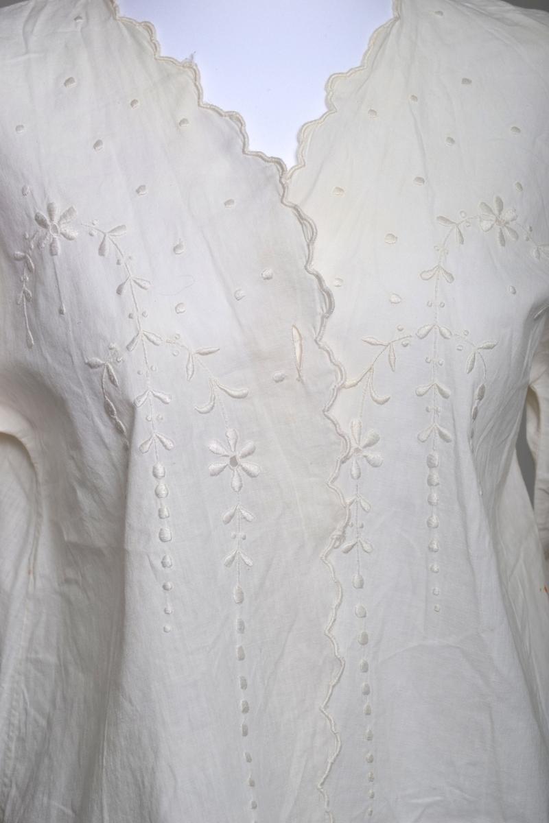 Nattkjole, kort i tynt bomullsstoff med vide halvlange ermer og ett knapphull på hver side av halsen. Dekorert med plattsøm og kantet med tungesting.