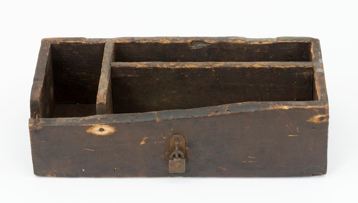 Trekasse, sist brukt til oppbevaring av materiell i ei smie.  Kassa er rektangulær, 50,7 centimeter lang, 24,2 centimeter bred og 15,0 centimeter høy. Innvendig er det innsatt skillevegger i en litt asymmetrisk T-form, slik at oppbevaringsvolumet er delt i tre rom. Spor etter gangjern på overkanten av den ene lagsida og et hengelås på fronten av motsatt langside kan tyde på at dette opprinnelig har vært et skrin med lokk. Den fremre langsida er ikke lenger komplett – en del av oversida er borte, antakelig etter en sprekkskade. Slitasjen på bruddflata tyder på at dette er en gammel skade. Alle trekomponenter er brunmalte.  Låsemekanikken på hengelåset er innkapslet i et messinghylster som er merket med to konsentriske ringer. I den innerste av dem finner vi tre B-er. Nøkkelhullet later til å være gjenrustet. Kassa, inkludert det nevnte hengelåset, men uten innholdet av jernkomponenter, veier 3,4 kilo.