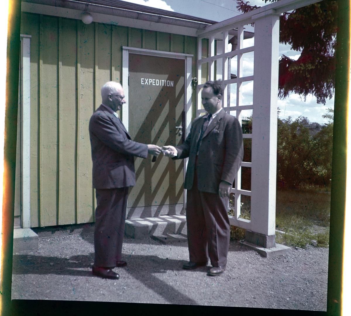 Negativ på två män utanför en byggnad i Folkets Park i Linköping. Personerna är Herman E. Nilsson och Alvar Vincent.