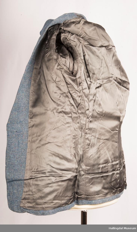Blågrå spettete dressjakke (16 år) med spensel i ryggen og med skrå lommer uten klaff.  Lukket med 1 plastknapp. 1 plaskanpp på hver erme og med 2 plastknapper på spensel bak.