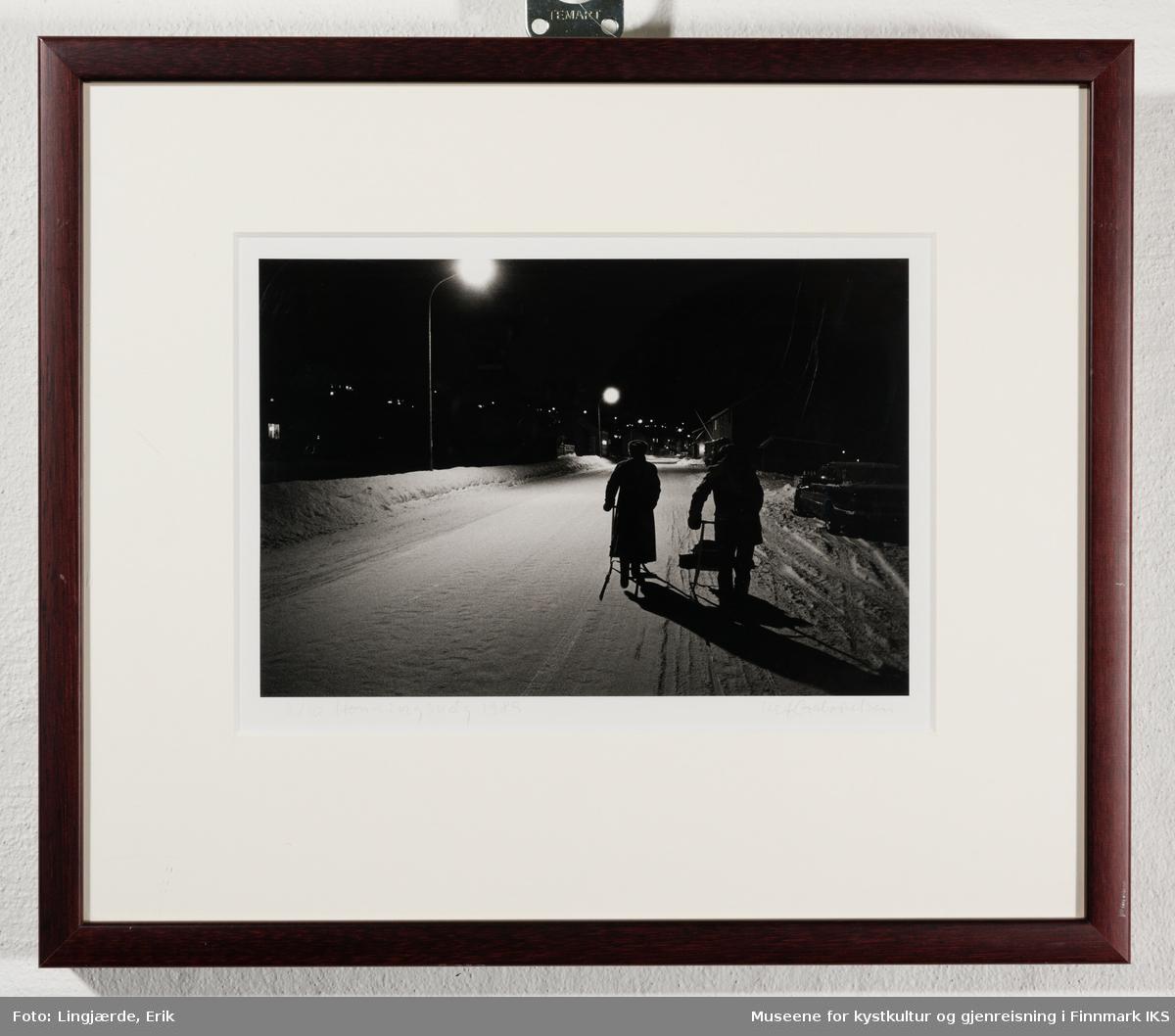 Vinter. To personer med spark på Nordvågveien i Honningsvåg.