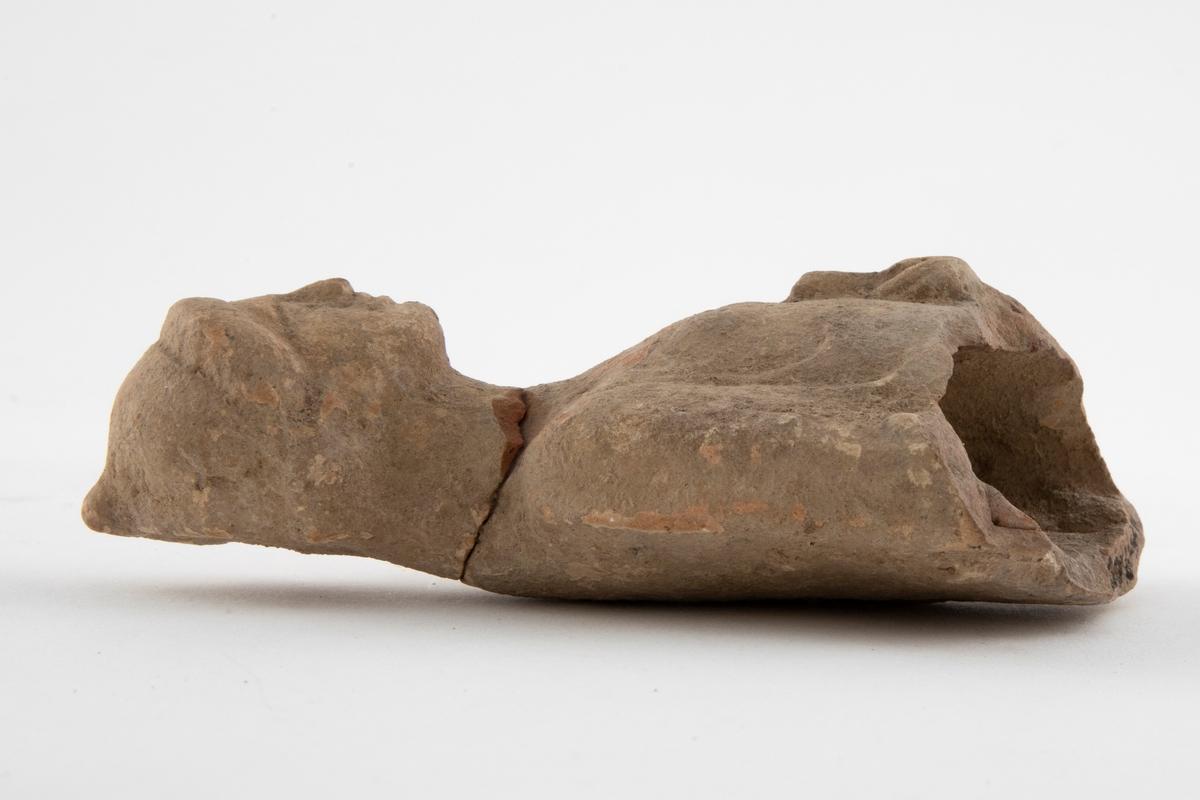 Fragment av figurin i terrakotta, øvre halvdel av kroppen er bevart. Fremstiller en kvinne iført drakt med oppsatt hår. Hun holder en eske i venstre arm. Figurinen har brudd ved halsen, og er senere limt. Lyst, rødlig gods, med grålige partier.