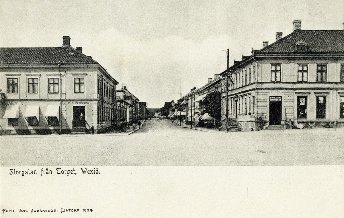 Storgatan från Stortorget, Växjö 1905, med vy västerut. Till vänster syns dåv. P.N. Perssons affär i kvarteret Unaman (Unaman 2) och till höger dåv. Wittlockska fastigheten i kvarteret Sunaman (Sunaman 3).  Vykort.  'Wittlock' - Johan August Zakarias Wittlock (1828-1910). Regementsläkare, kv. Sunaman 3, Växjö.  (Källa: Folkräkning 1890 och 1900, Växjö stadsfs, Riksarkivet. Sveriges Dödbok 1860-2017)