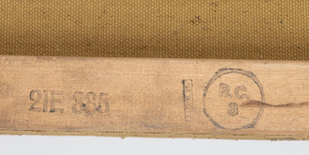 Sykebåre med tilskårne håndtak. To bærestenger med lerret/seilduk i mellom. Leddet metallstag i hver ende av duken. Sykebåren lå på loftet til Son skole. Vi antar at den har tilhørt et lager for Sivilforsvaret eller Røde Kors.  Gitt til Follo Museum av Vestby kommune.