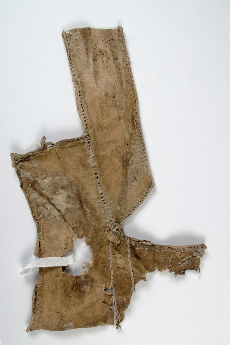 Fragment av pälsplagg, rester av ull på insidan. Sannolikt mansväst med halv ståndkrage och en liten del av framstycket med ärmringing och ett knapphål.