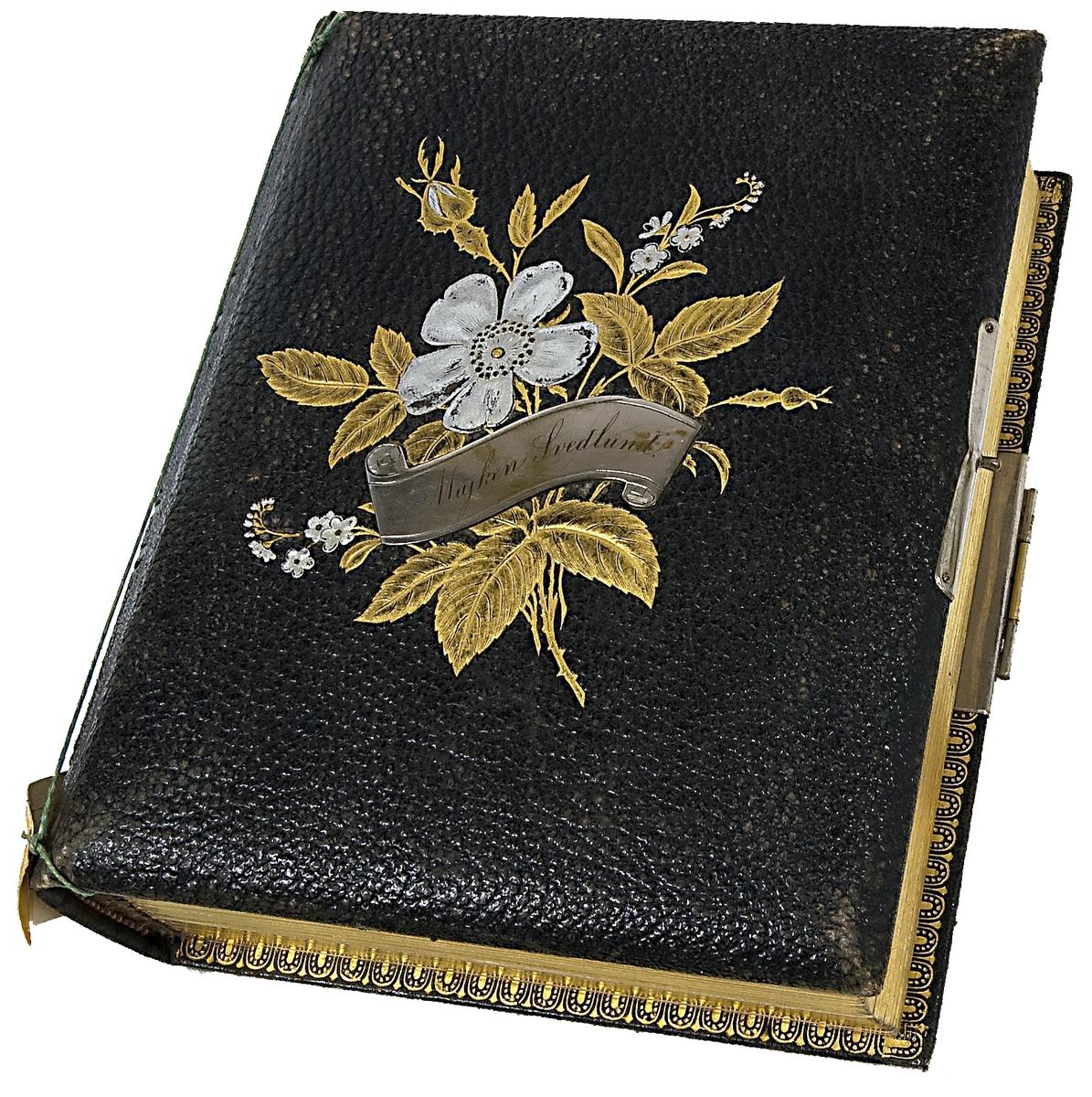 Fotoalbum, svart läder. Dekoration: blombukett med förgyllda blad och försilvrade blommor och namnskylt Majken Svedlund.