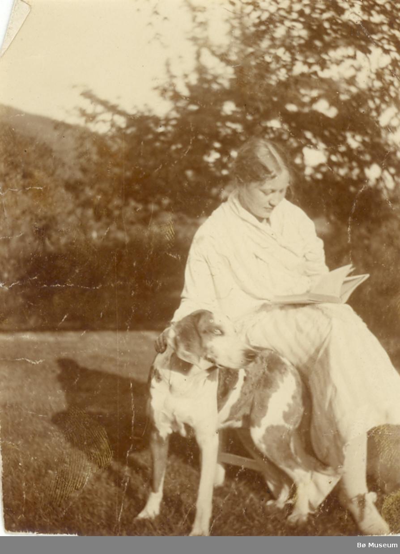 Ingebjørg T. Valen, Bø,  sitjande ute i hagen med hund