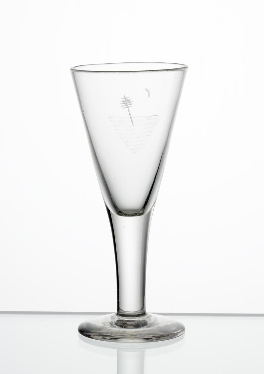 Brännvinsglas, konisk kupa på draget ben och skivfot. Graverat motiv bestående av sjömärke med månskära i bakgrunden.