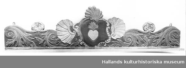 Hylla av trä. Brunlackerad avställningsbräda. Profilerat och målat överstycke dekorerat med musslor, akantus, hjärta mm.