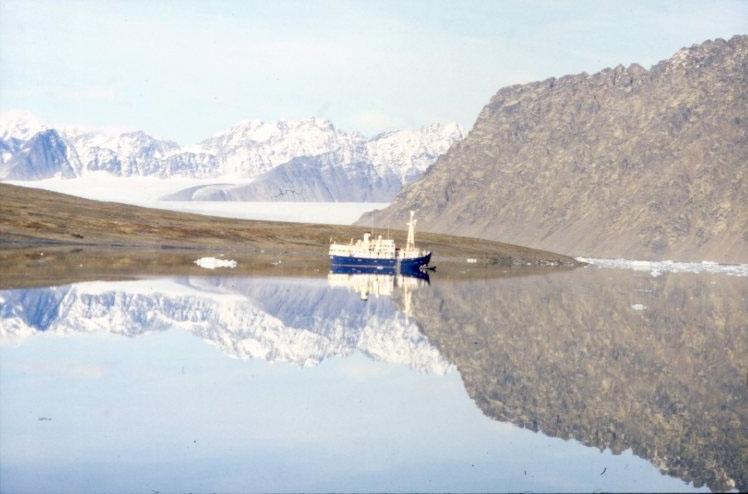 Expeditionsfartyget M/S Origo ligger för ankar i Signehamna och speglar sig i ett mycket stilla vatten.