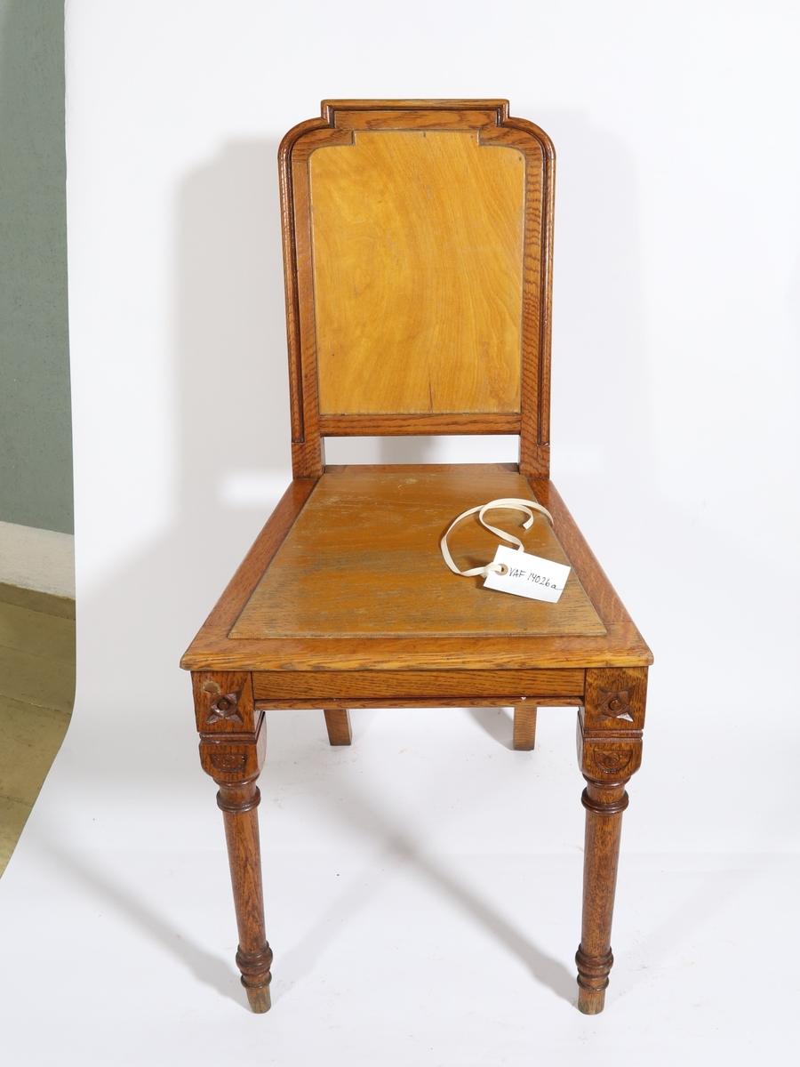 Stoler av tre. Trapesformet sete og dreide stolben med utskjæring som ligner stiliserte fire-kantede blomster.  Merker etter fester til rotting på stolrygg og sete viser at disse tidligere har hatt sete og stolrygg trukket med rotting. Merking på en av stolene viser at de har tilhørt Den Norske Bank.  d) har polstret sete trukket med grønn tekstil.