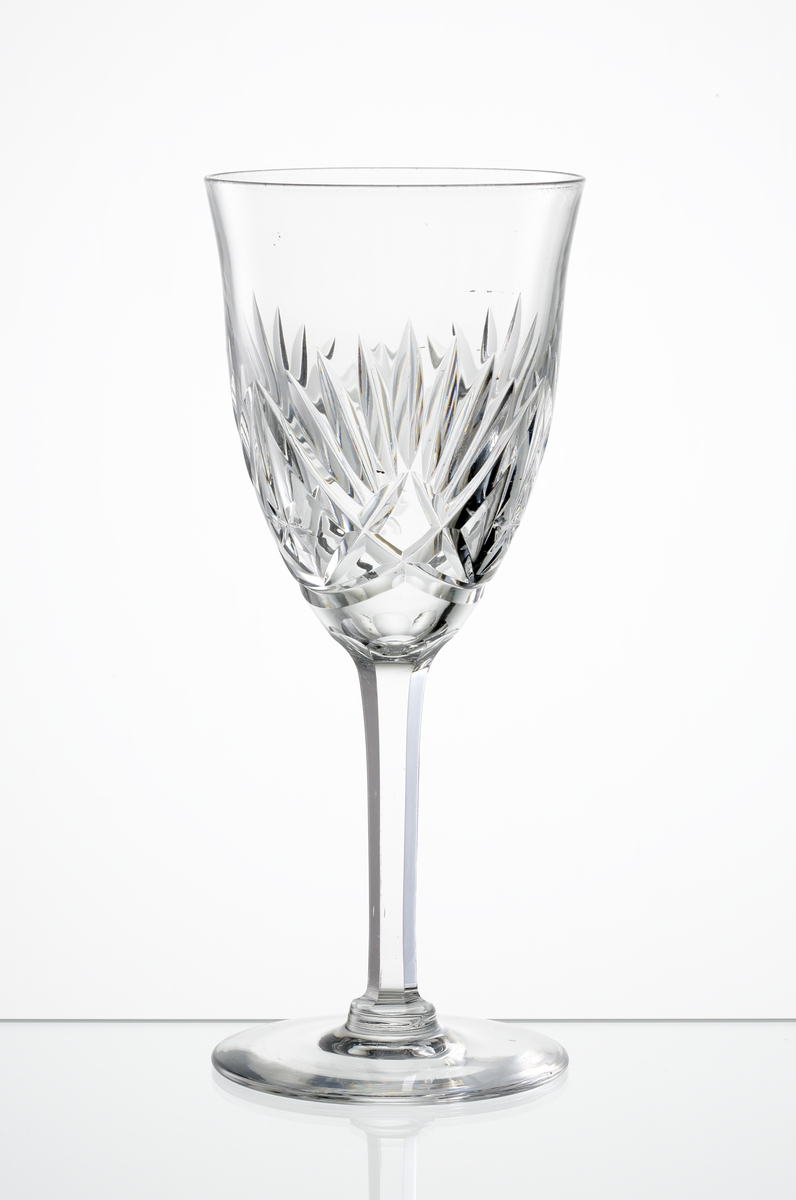 Rödvinsglas, svagt klockformad kupa med skärslipad dekor. Högt fasettslipat ben med slät fot.
