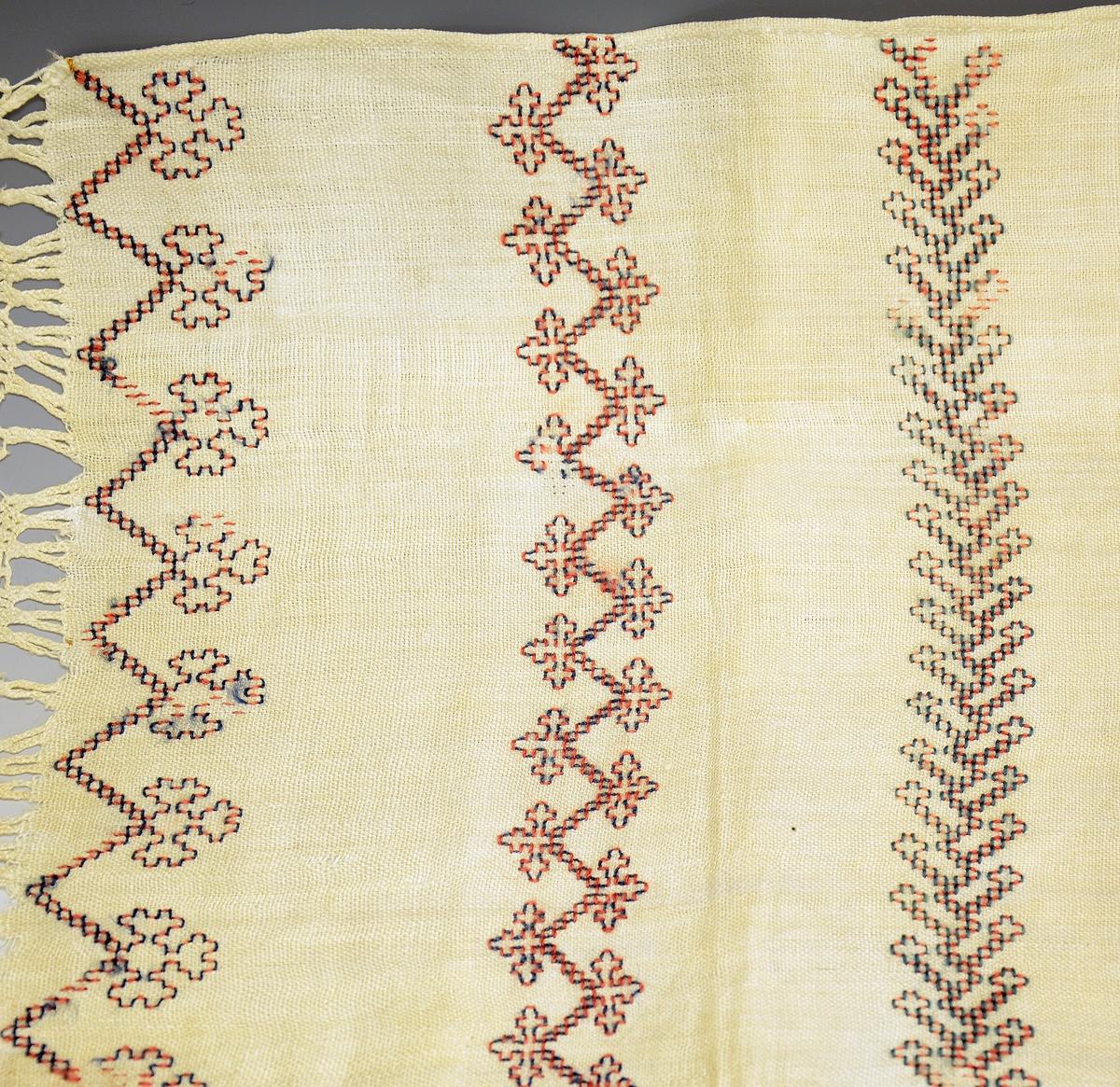 Kisteklede. Fra protokollen: Likkisteklæde. Hvitt linklæde med et stort kors syet midt paa. I hver ende av klæde to border, og en knyttet fletning (som paa haandklæder). Korset er fyldt med krokmønster av av kulørt uldsøm, samme mønster i borden.