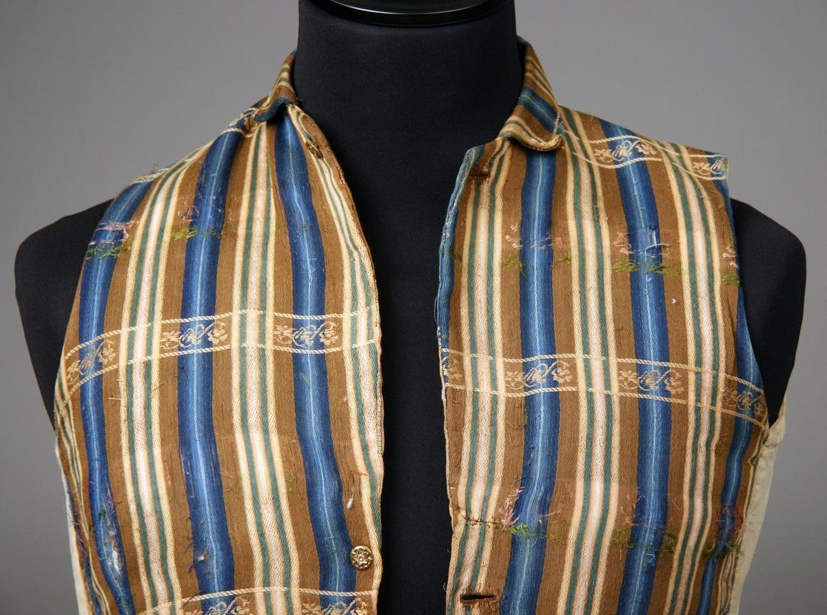 Mansväst av randigt mönstervävt ylletyg i blått, brunt, grönt och rosa. Smal nervikt krage, metallknappar med blommönster och rester av färg i blått och rött. Rygg av linnelärft och linnekypert.
