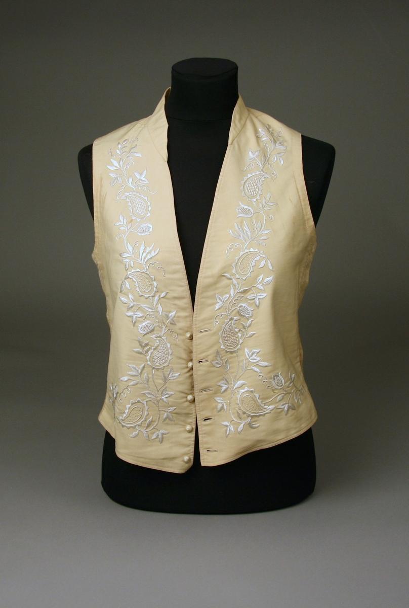 Mansväst av fint vitt ylle, med sidenbroderier i vitt silke utförda i stjälkstygn, plattsöm m.m. Ryggstycke av bomullstyg eller linne i samma färg.