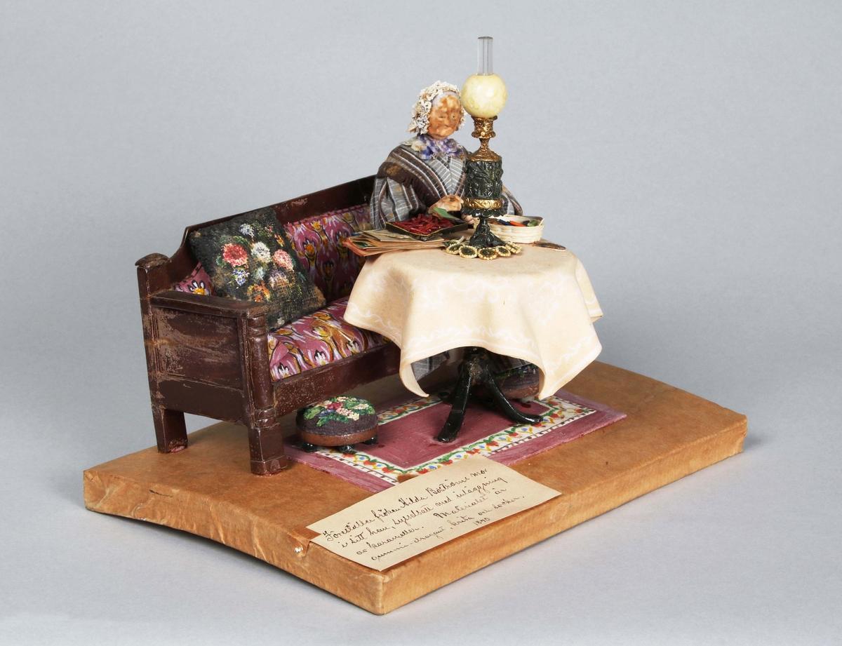 Dragantarbete. Figurgrupp. Föreställer Hedda Boström, sittande i soffa sysselsatt med inläggning av karameller i sitt hem. Iförd grå klänning med bruna ränder på längden, långa ärmar med manschetter, samt vid kjol. Vit spetskrage, lilafärgad halsduk och vit spetsmössa. Schal av liknande tyg som klänningen med brun frans. Soffgrupp bestående av soffa, bord samt 2 stycken pallar. Soffan har bruna karmar och lilafärgad botten med mönster i gult och vitt, samt en ensam broderad kudde, med polykroma blommor mot svart botten. Pallarnas översida broderade som kudden. De står på vardera 5 svarta kulfötter. Bordet med ljus bordsduk, lilafärgad matta med mönsterrand (vit botten med mönster i rött, grönt, blått, gult och vitt). Föremål på bordet: Fotogenlampa i svart, guld och vitt, sax, glasögonfodral, glasögon, 1 exemplar av Borås Tidning, pappershög, samt en svart och en vit skål med papper till karameller.   Gruppen förvaras, under fyrsidig, rektangulär glasmonter. Mått: 205x205x145 mm. Pappersklätt underlag.   Handskriven etikett till vänster med text: Föreställer Fröken Hilda Boströms mor i sitt hem, sysselsatt med inläggning av karameller.   Tillverkad år 1840, av Hilda Boström 1822-1903), sockerbagare, Borås.  Litt: Se Årsbok 1963, sidan 45.  Funktion: Prydnadsfigurin