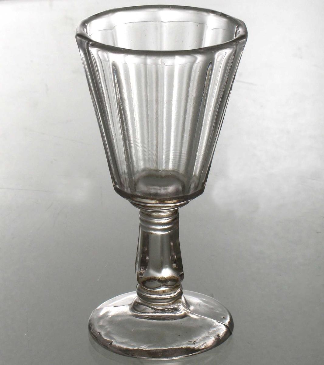 Hetvinsglass. Pressglass. Rund glatt fot med støperand tvers over.  Kantet stett med en ring nede og tre oppe.  Kantet beger med skrå, rette sider.
