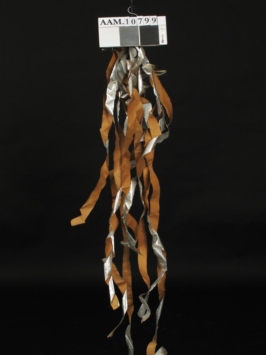 Papirstrimler, sølvpapirbelagte, engelske, fra krigen 1940-45. En haug   papirbånd, brunt på den ene side, sølv på den annen. Tilstand: endel sammenkrøllet,ellers bra.  Prov. Sluppet ned fra engelske fly under krigen  1940-45 i skogen rundt Åmli (funnet i giverens skog),  for å villede tysk radar ved flyfotografering.