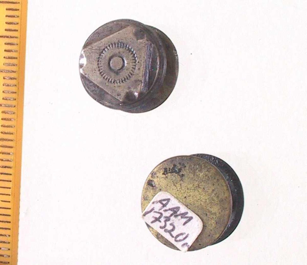 Mansjettknapper,   Sølv  og   messing.  2 doble knapper, bestående av 2  flate skiver med tverrstang.  På den ene x skive en trekantet plate  av sølv dekoevrt med takket sirkel.  Innk.1.juli 1977.   Lå i skrinet med sytråd,  signeter etc.