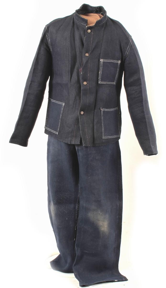 Drakt, arbeidsklær, bukse og jakke.  Sydd av tøy som er vevd av papirtråder. Trykknapper av metall. Deler: a) jakke  b) bukse Innskriften er på en fastbundet lapp. Buksa er brukt, den er tilgriset på knærne, mens jakka ikke bærer preg av bruk, prislappen henger på.