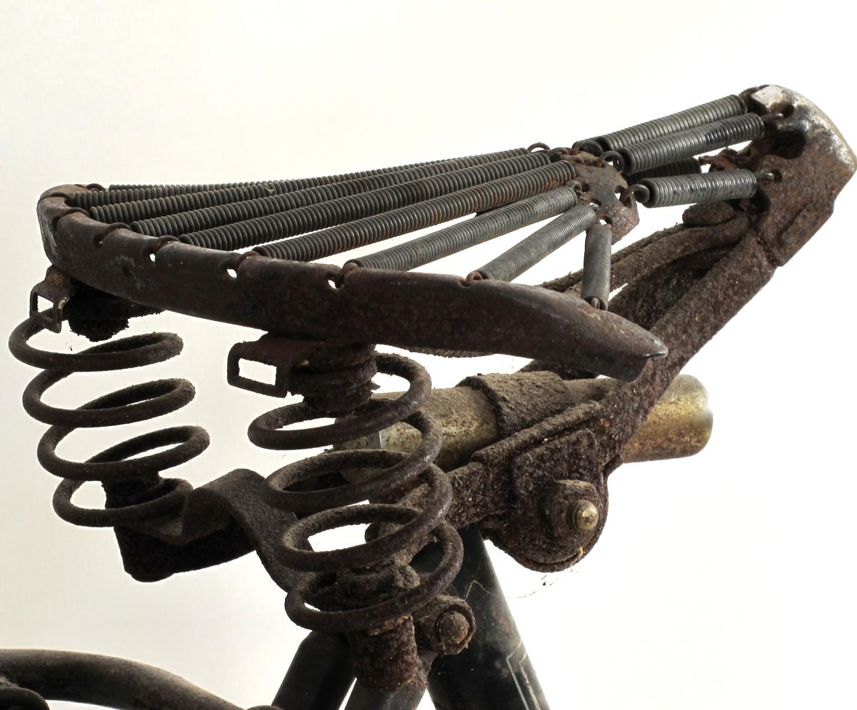 Sykkelen  er utstyrt med sidestøtte, relativt nye dekk og har rester av nett på bakhjulene. Fint produsentemblem på forskjermen, med bokstaven S og en vinge som motiv.  Staffage, linjer og flater malt i grønt og hvitt. Middels. Noe rust. Ikke org.bakhjulsfelg.
