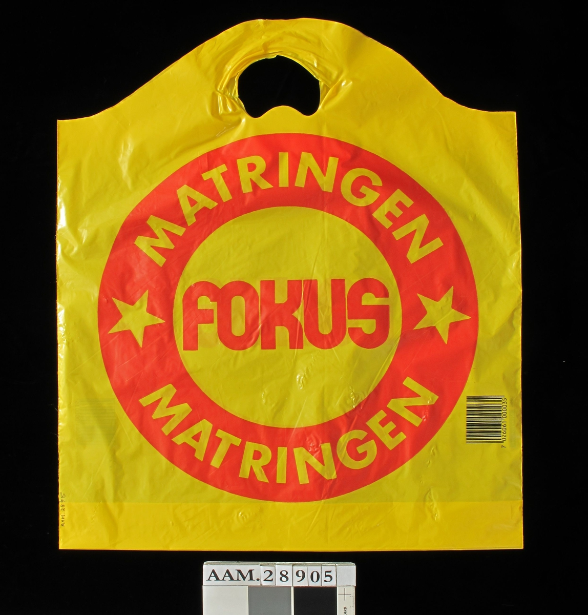 Bærepose for dagligvarer. Fokus-kjeden. Gul pose med en stor rød ring. Tekst på og i ringen. Stekkode.
