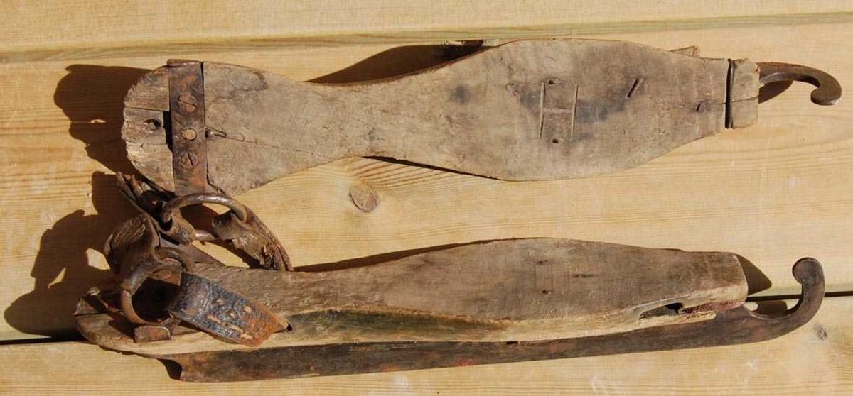 Skøytejern satt inn i tresåler. Jernet er festet med skrue i bakkant.  Med unntak av bakre rem på den ene skøyten, er alle remmer borte.