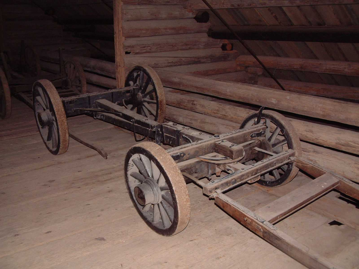 Understell bestående av bakvogn og framvogn med svingflak. Akslingene er forbundet med mellomstang. Jernbeslåtte trehjul med svak styrt. Faste, forholdsvis lave, jernkeiper. Originalt drag.