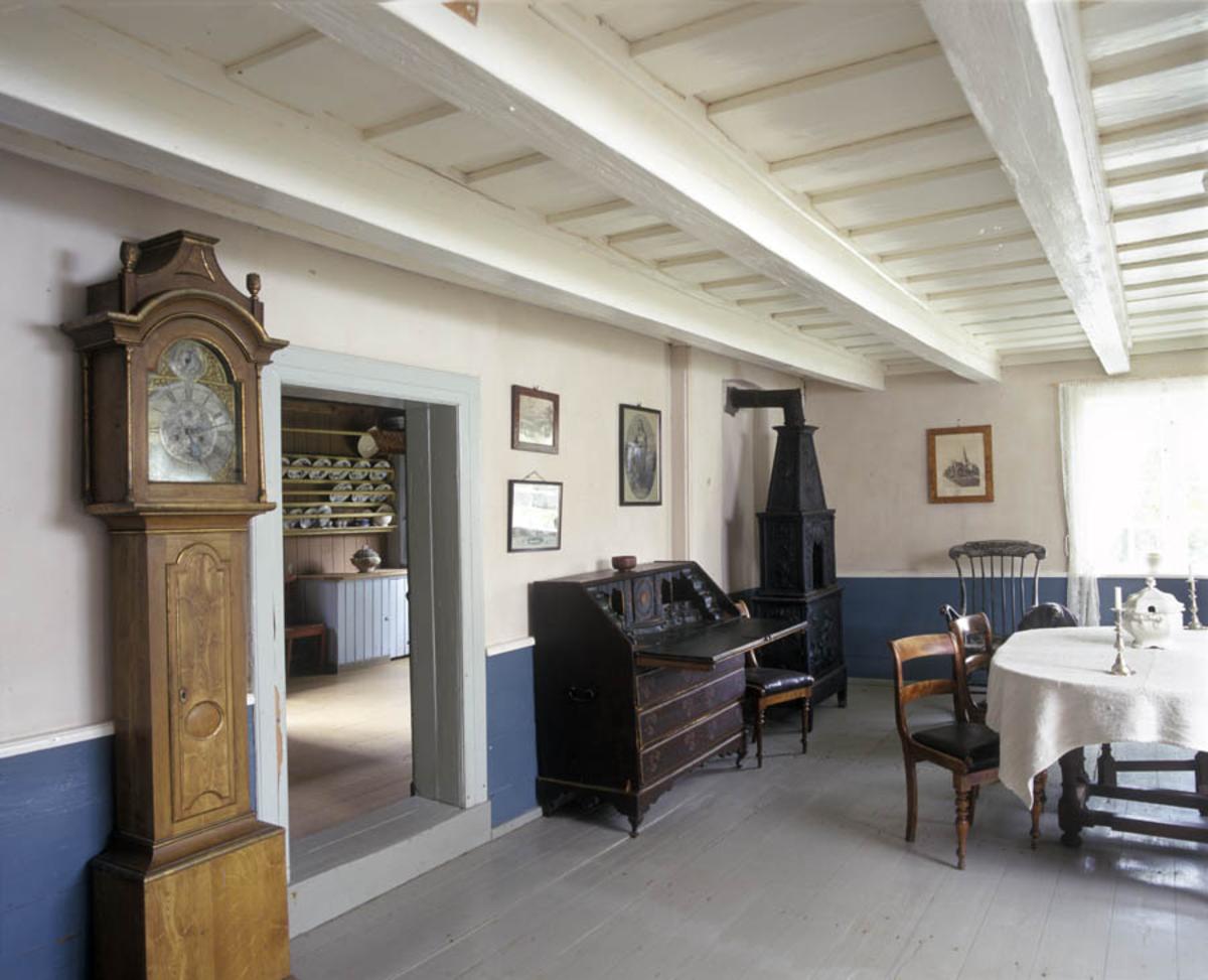 Follo museum, Børsum huset. Interiør. Finstue, gulvur, skjatoll, støpejernsovn, spisebord.