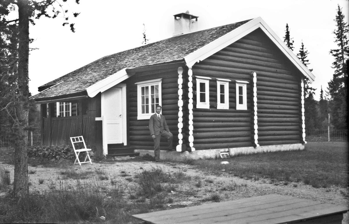 Mann utenfor tømmerhus eller –hytte.