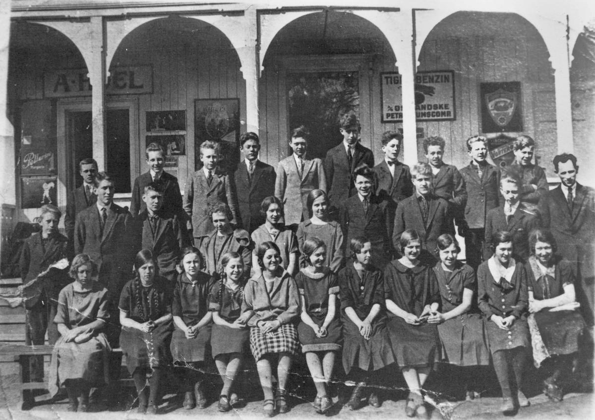 Stor gruppe jenter og gutter. Bildet tatt utenfor A Hoel landhandel og bensinstasjon. Navnet Jens Bønsdalen er notert på bildet.