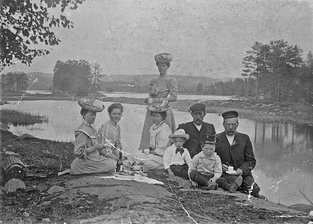 Utflukt ved innsjø. Ca. 1905.  Kvinnen som står er Marie Halvorsen. Mannen som sitter ved siden av henne er Olav Halvorsen. De andre er ukjent.
