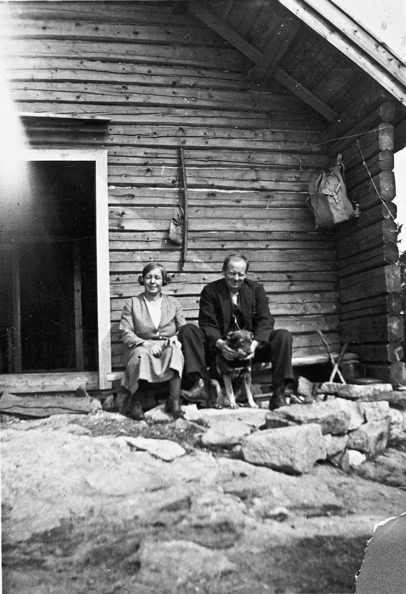 Kvinne og mann utenfor et tømmerhus.