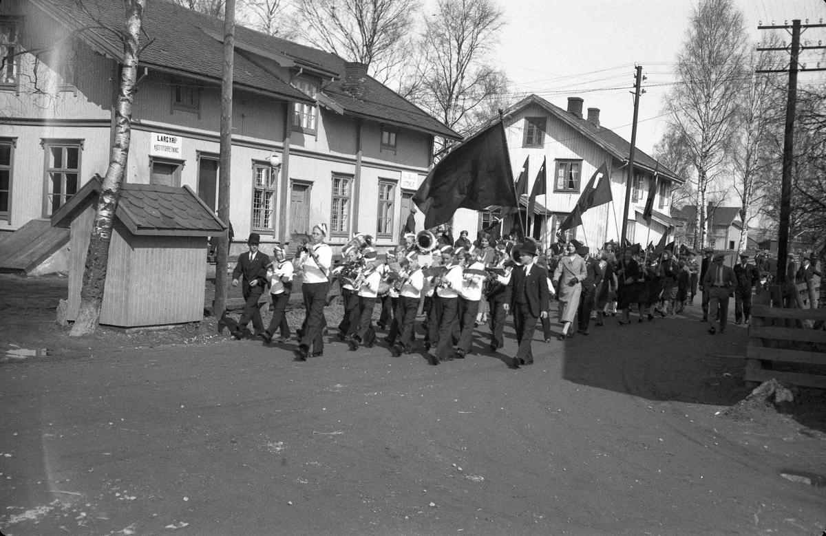 Korps marsjerer foran 1. maitog på Bøn foran LARS YRI kjøttforretning. Bilde fra før krigen.