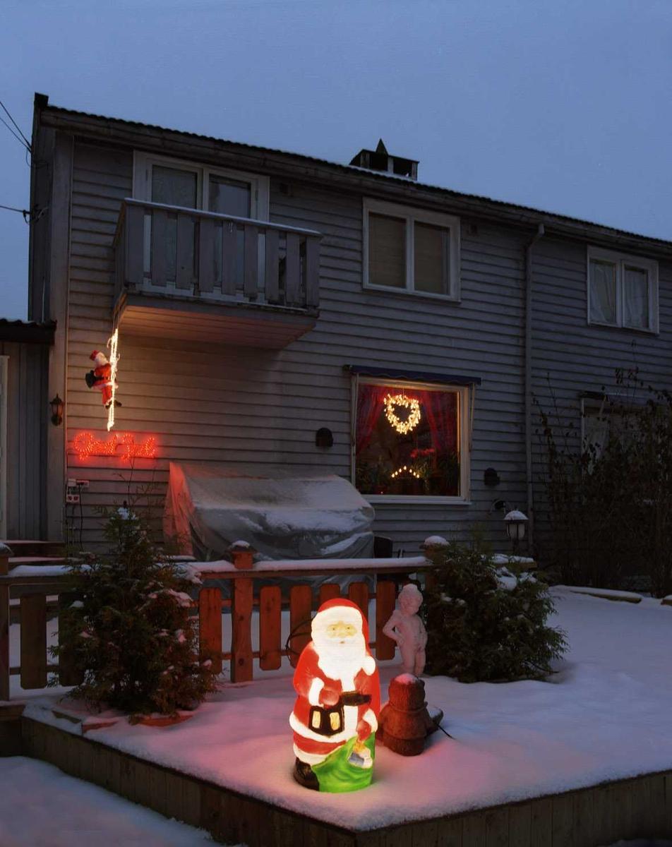 Julebelysning.    Lysende nisse på veranda og klatrende nisse på husvegg på rekkehus. Lysende krans i vindu