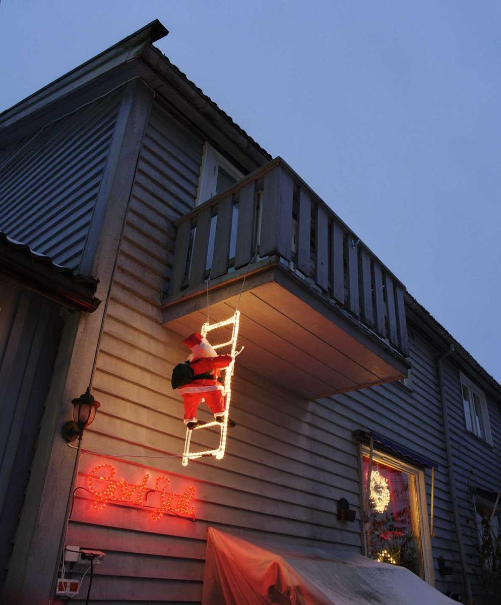 Julebelysning.    Klatrende nisse og rød lysende skrift med god jul på husvegg på rekkehus. Lysende krans i vindu