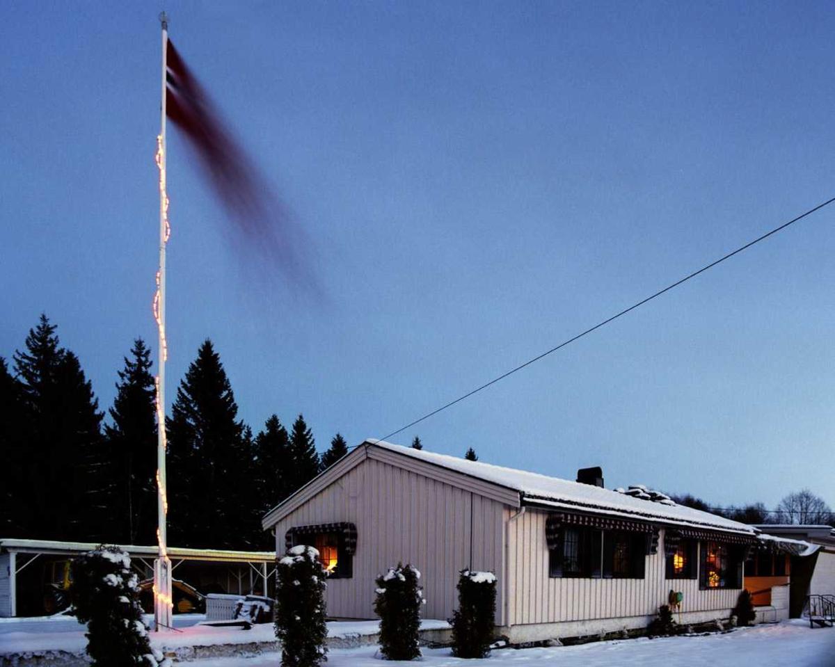 Julebelysning  Flerfarget lysslange rundt flaggstang ved enebolig.