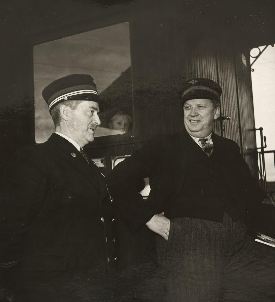 Stasjonsmesteren slår av en prat med en reisende (som har fått låne en uniformslue)