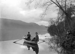 To menn med bowlerhatt i robåt.