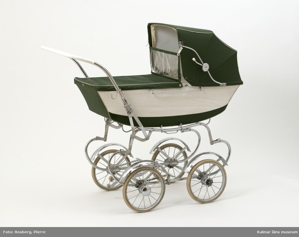 KLM 39807:1. Barnvagn, liggvagn. Tillverkad av Emmaljunga, Nr 119. Barnvagn med underrede av metall, gummiklädda hjul med text; Emmaljunga Trelleborg. Liggvagn med träbotten, sufflett och skyddstyg av grönt och vitt galonliknande material. Sömmarna är dekorerade med guldfärgad plast. Inuti vagnen en ligger en tillhörande madrass (KLM 39807:2).